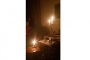 بالصور ... مواطنون يسهرون من دون كهرباء وحلاق يعمل على ضوء الشمعة