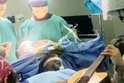 مريض يعزف الجيتار أثناء خضوعه لجراحة في المخ